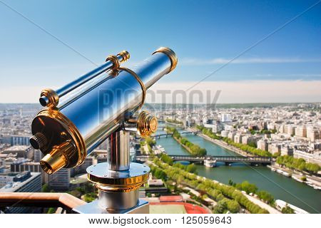 Telescope on the viewpoint with view of the Seine river and its green banks. Panoramic view of Paris in sunny weather with blue sky and the river.