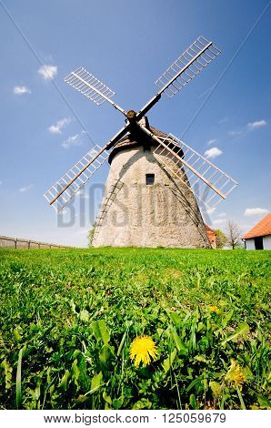 Historic windmill in the Czech countryside, Kuzelov, Bile Karpaty (The White Carpathians). Windmill on the meadow with flowering dandelion.