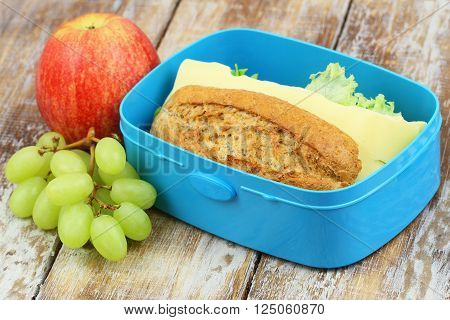 School lunch box consisting of brown bread sandwich with cheese, apple and grapes