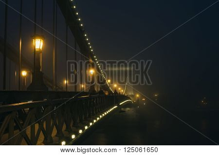 Chain Bridge in Budapest, Hungary, in evening lights, on a foggy day. Shot from the Pest side of the Danube river