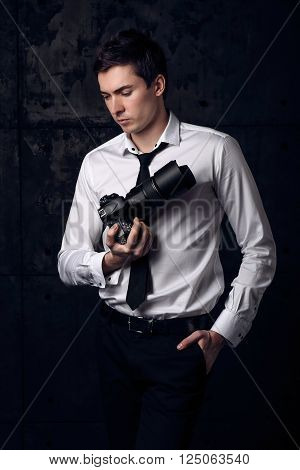 Art portrait of photographer in studio with his digital camera