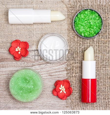 Cosmetics for lip skin care: sea salt, natural honey scrub with essential oils, moisturizing lip cream and balms with flowers on shabby wooden surface and sackcloth napkins