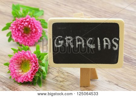 Gracias (which means thank you in Spanish) written with wooden letters and pink dahlia flower