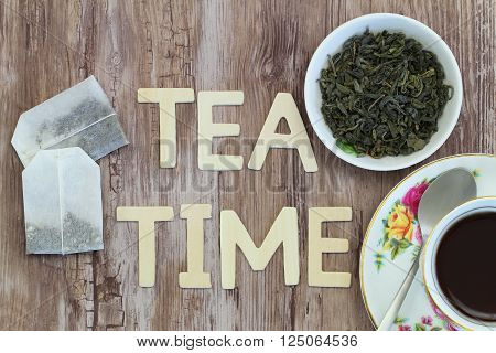 Tea time written with wooden letters, tea bags and dried tea leaves