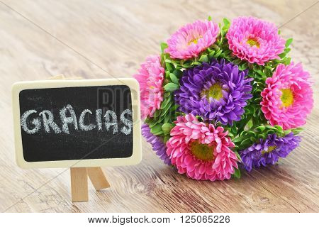 Gracias (which means thank you in Spanish) written on mini blackboard with colorful aster bouquet
