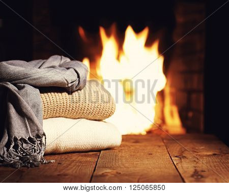 Warm Woolen Things Near Fireplace On Wooden Table.