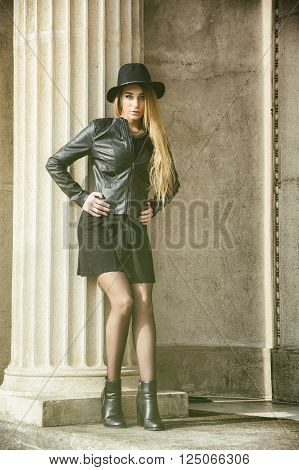 Portrait of attractive blonde young woman in black fedora hat and leather jacket looking at camera