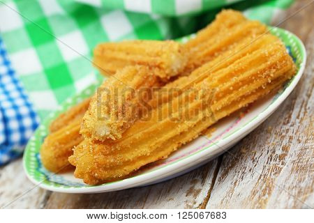 Spanish churros sprinkled with sugar and cinnamon on plate