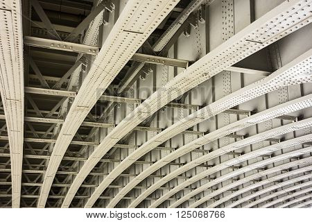 The underside of a bridge in London shows the architectural details of a geometric pattern of curved beams and girders that provide infrastructre support for the road abovve.