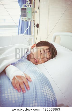 Asian Boy Lying On Sickbed With Saline Intravenous (iv). Health Care And People Concept.