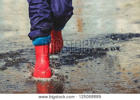 Child with red boots is jumping into a puddle in raining spring or autumn outdoor. Toning instagram filter.