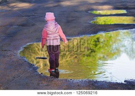 Back view of walking in spring puddle preschooler girl is wearing purple nylon coat and pink bucket hat