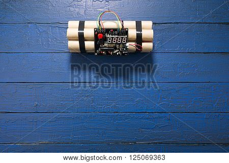 TNT bomb explosive with digital countdown timer clock over blue background.