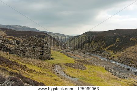 Spring sunshine breaks through cloud to shine on a ruined smelting mill works at Surrender Bridge, Swaledale, Near Reeth, Yorkshire Dales National Park