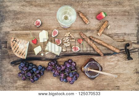Glass of white wine, cheese board, grapes, figs, strawberries, honey and bread sticks on rustic wooden background, top view, horizontal oriented