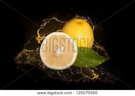 Fresh yellow grapefruit inside grapefruit juice splash, isolated on black background.