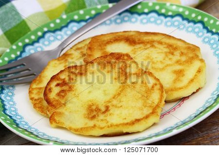 Golden potato fritters on plate, close up