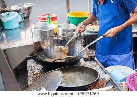 Chef cooks stir-fried noodles at Kimberly Street Food Night Market. George Town Penang Malaysia.