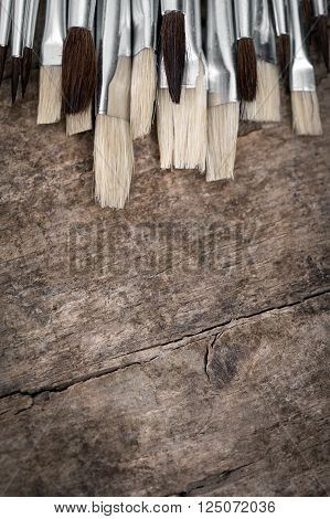 lot of unused brushes on a wooden background vintage filtered