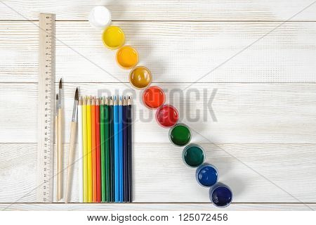 Top view of paint brushes with colorful gouache containers and pencils with centimeter ruler on a light wooden background.