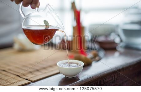 Pour tea from teapot transparent in white cup