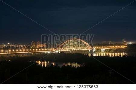 Bridge illuminated at night in Novosibirsk over the river