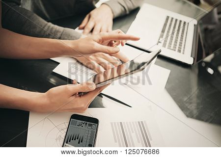 Business situation, meeting of financial analysts.Photo woman showing marketing reports tablet.Modern smartphone and laptop table.Working process office, discussion startup. Horizontal.