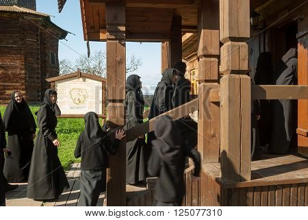 Suzdal, Russia - August 29, 2009: Novices of convent visit museum of wooden architecture