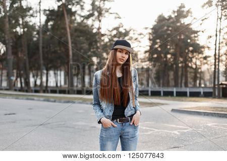 Young Beautiful Fashionable Woman In A Denim Jacket And Jeans Standing In A Park On A Sunny Day
