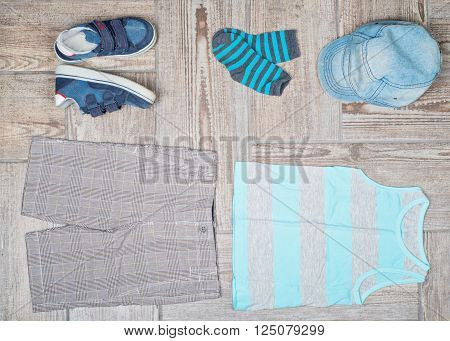 Flat lay photography of boy's casual outfit. Boy's casual outfit on wood board background