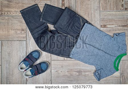 Flat lay photo of boy's casual outfit. Boy's casual outfit on wood board background