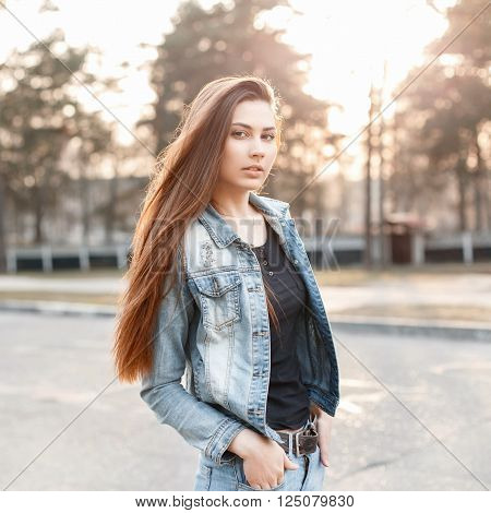 Young stylish girl in denim clothes at sunset.