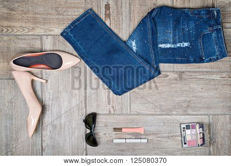 Flat lay photography of girl's jeans with accessories on wooden background