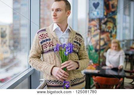 sad in love guy with holding flowers waiting for someone. man waiting for the boyfriend or girlfriend on a date. behind the man lonely girl sitting at a table in a cafe.