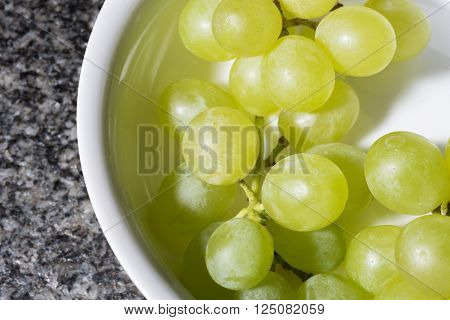 close up of tasty whine grapes on white background