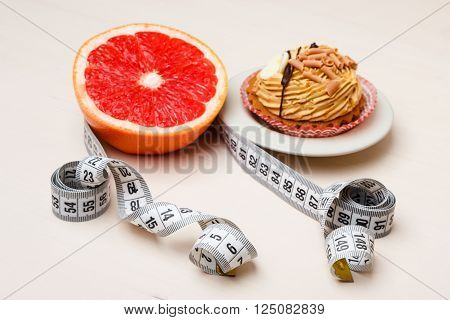 Concept of making choice: healthy low-calorie or unhealthy high-calorie food slimming or fattening. Grapefruit and cake cupcake with measuring tape