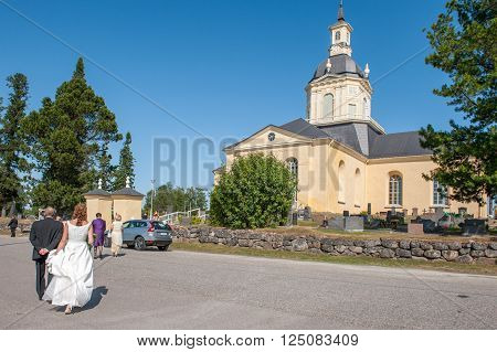 TORNIO, FINLAND - JULY 11: Bride and wedding guests approaching the church on July 11, 2009 in Tornio. The first church on this site was built in the 14th century and the current church dates back to 1797.