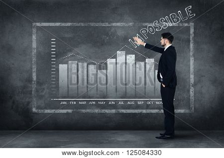 Everything is possible. Full length of confident young man in full suit standing near concrete wall and touching illustrated chart