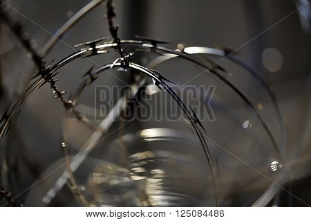 chain link security fence with barb and razor wire closeup