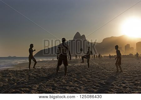 RIO DE JANEIRO, BRAZIL - APRIL 8: Silhouette of locals playing beach football on the shore of Ipanema Beach with Two Brothers Mountain on the Background on April 8, 2016, Rio de Janeiro, Brazil