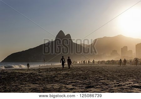RIO DE JANEIRO, BRAZIL - APRIL 8: Silhouette of local surfers walking on the sand of Ipanema beach in the afternoon with Two Brothers Mountain on the background April 8, 2016 in Rio de Janeiro, Brazil.