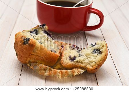Closeup of a blueberry muffin with a cup of coffee in the background. The muffin is broken in half on a rustic white wood table.