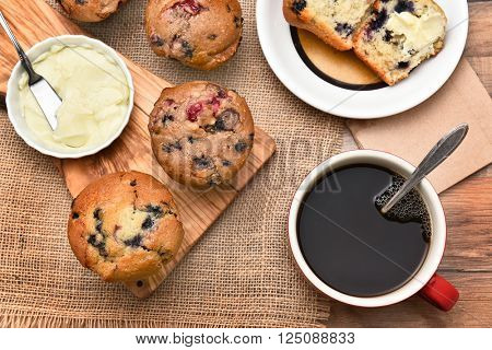 Top view of a breakfast table with assorted muffins, coffee and butter. Items are on a wood table with burlap table cloth.