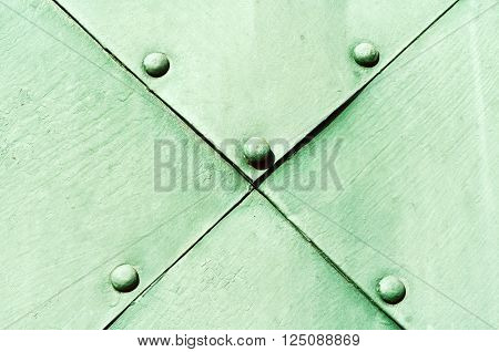 Steel pale green superficies of old carved metal plates with round rivets on them. Metallic textured background.