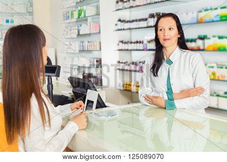 Pharmacist suggesting medical drug to buyer in pharmacy drugstore selective focus