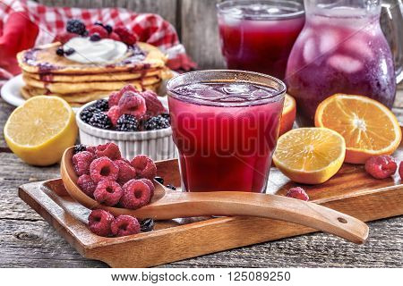 juice of raspberries and blackberries with citrus and pancakes on the table