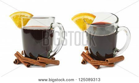 Glass of mulled wine decorated with the cinnamon sticks and slice of orange, composition isolated over the white background, set of two different foreshortenings
