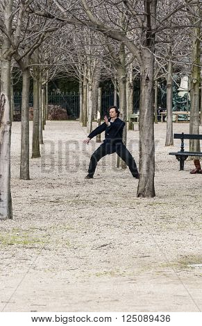 PARIS - MARCH 2: a man doing his exercise for oriental discipline in a park on March 2, 2014 in Paris France