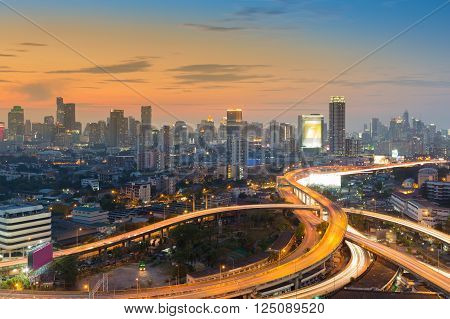 Beauty of sunset sky over city downtown background and road interchange, long exposure