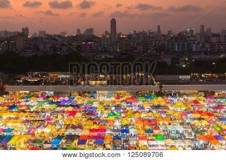 Aerial view colourful flea market roof top with city downtown background during sunset